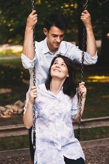 Glimlachend paar in liefde op een schommeling die in openlucht aan elkaar kijkt