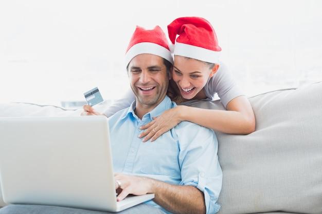Glimlachend paar in santahoeden die online met laptop winkelen