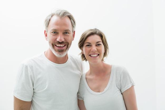 Glimlachend paar in wit t-shirt in slaapkamer thuis