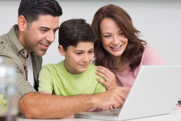 Glimlachend paar met zoon die laptop met behulp van
