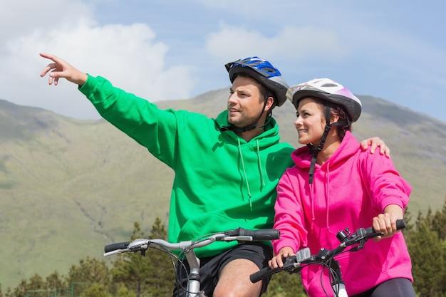 Glimlachend paar op een fietsrit die verbindingsdraden met een kap met mens het richten dragen