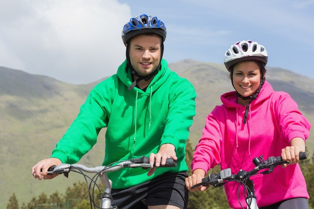 Glimlachend paar op een fietstocht dragen hooded jumpers