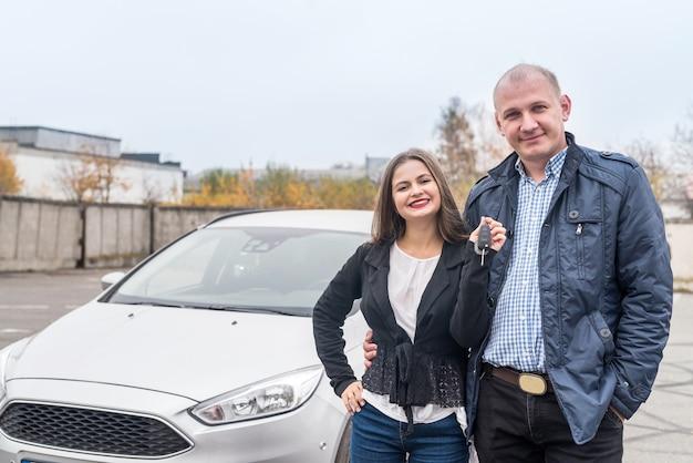 Glimlachend paar poseren in de buurt van nieuwe auto met sleutels
