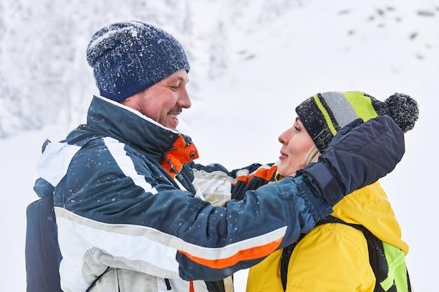 Glimlachend paar reizigers kijken elkaar aan op de achtergrond van een wazig winterlandschap