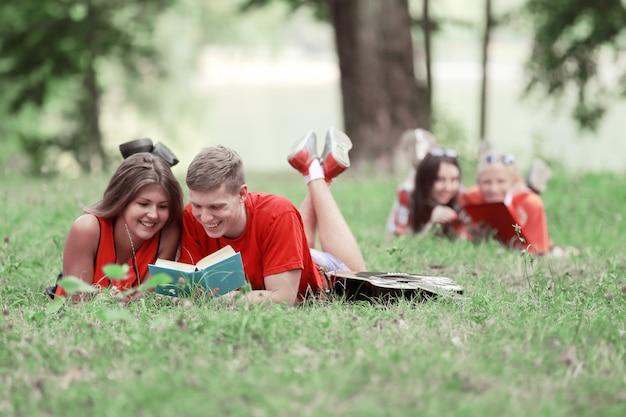 Glimlachend paar studenten die een boek lezen dat op het gras ligt.