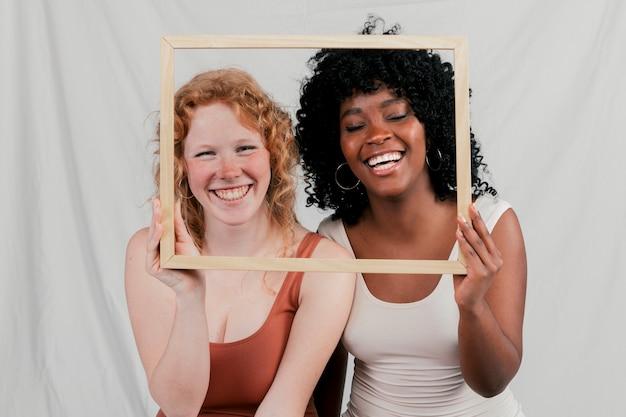 Glimlachend portret van blonde en afrikaanse jonge vrouwen die houten kader voor hun gezicht houden