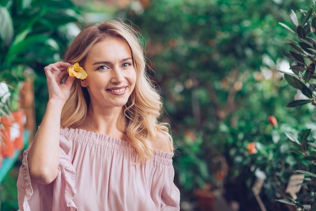 Glimlachend portret van blonde jonge vrouw die gele bloem in haar oor houdt