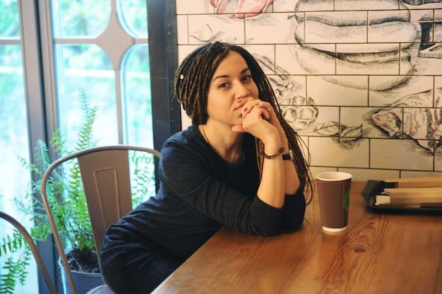 Glimlachend portret van de jonge vrouw met dreadlocks en kopje koffie, zittend in café