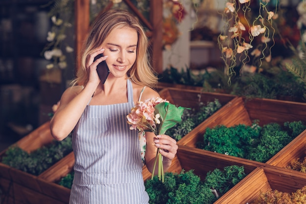 Glimlachend portret van een bloemist roze hortensia in hand praten op mobiele telefoon