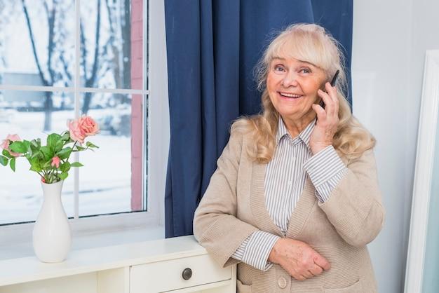 Glimlachend portret van een hogere vrouw die zich dichtbij het venster bevindt dat op celtelefoon spreekt