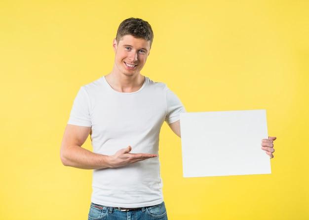Glimlachend portret van een jonge mens die iets op witte lege kaart voorleggen tegen gele achtergrond