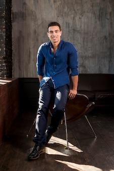 Glimlachend portret van een jonge mens die op stoel leunt die camera bekijkt