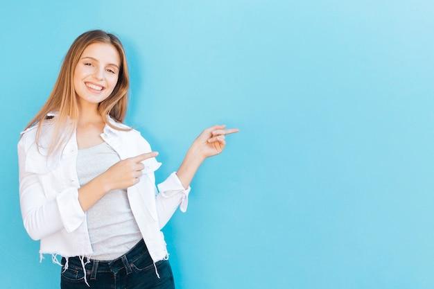 Glimlachend portret van een jonge vrouw die haar vinger richt tegen blauwe achtergrond