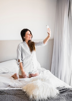 Glimlachend portret van een jonge vrouw die op bed knielen die selfie over mobiele telefoon nemen
