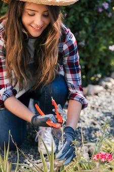Glimlachend portret van een jonge vrouwelijke tuinman die het takje in orde maken met scharen