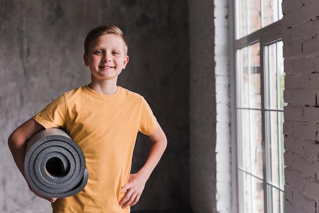 Glimlachend portret van een jongen die grijs opgerolde oefeningsmat houdt