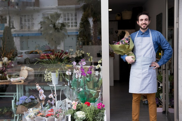 Glimlachend portret van een mannelijk boeket die van de holdingsbloem zich bij de ingang van bloemistwinkel bevinden