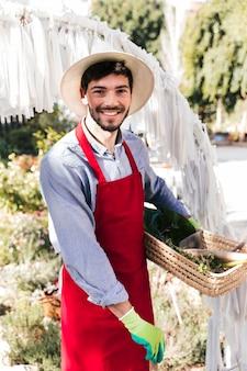 Glimlachend portret van een mannelijke tuinman die in rode schort camera bekijkt