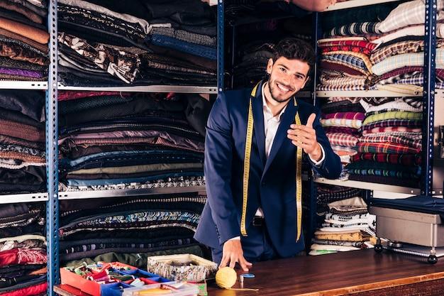 Glimlachend portret van een mannelijke uitnodigende klant in zijn winkel