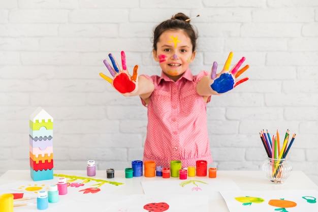 Glimlachend portret van een meisje dat haar geschilderde kleurrijke hand aan camera toont