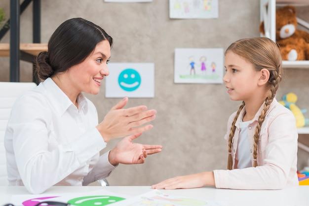 Glimlachend portret van een meisje en een vrouwelijke psycholoog die gesprek in het bureau hebben