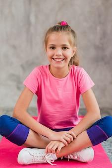 Glimlachend portret van een meisjeszitting op roze tapijt tegen grijze concrete muur