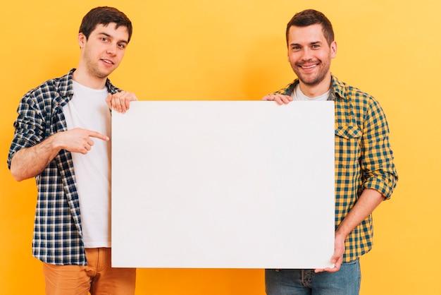 Glimlachend portret van een mens die wit leeg aanplakbiljet toont tegen gele achtergrond