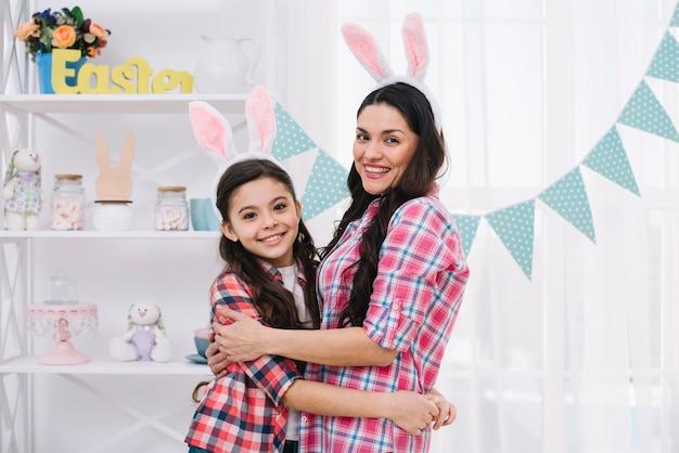 Glimlachend portret van een moeder en een dochter die elkaar thuis omhelzen
