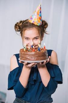 Glimlachend portret van een tiener die de cake van de holdingschocolade van de partijhoed op plaat dragen