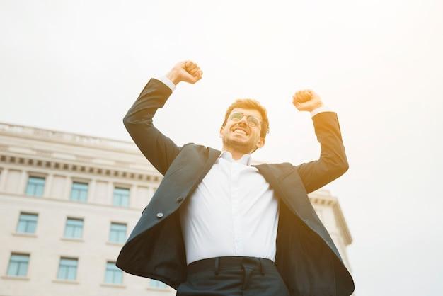 Glimlachend portret van een vrolijke jonge zakenman balde zijn vuist