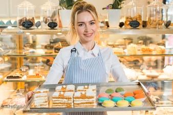 Glimlachend portret van een vrouwelijke bakker die groot dienblad met kleurrijke makarons en gebakjes houdt