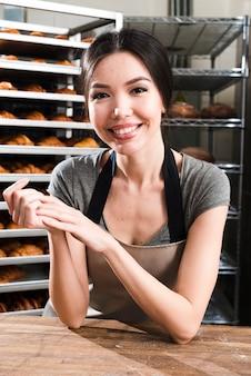 Glimlachend portret van een vrouwelijke bakker die schort draagt die camera bekijkt