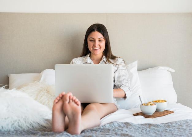 Glimlachend portret van een vrouwenzitting op bed met gezond ontbijt die laptop met behulp van