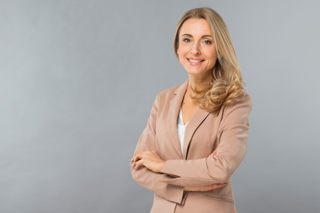 Glimlachend portret van een zekere blonde jonge vrouw die zich tegen grijze achtergrond bevindt