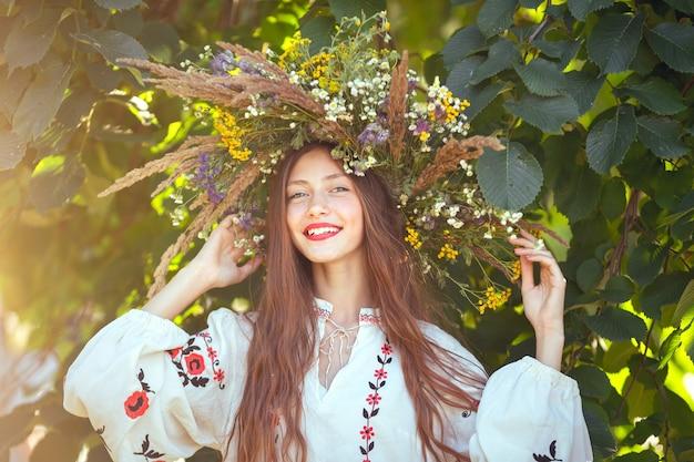 Glimlachend portret van mooi meisje in krans van bloemen in weide op zonnige dag.