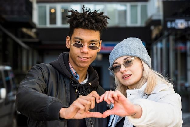Glimlachend portret van paar tussen verschillende rassen die zonnebril dragen die hartvorm met hun handen maken