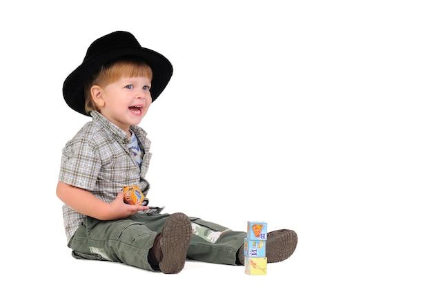 Glimlachend positief jongetje in een zwarte hoed speelt blokjes zittend op de vloer op een witte achtergrond