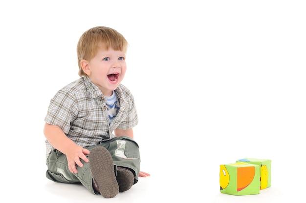 Glimlachend positief jongetje speelt kubussen zittend op de vloer op een witte achtergrond
