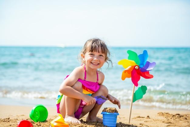 Glimlachend positief meisje een veelkleurig zwempak en een vuurradregenboog ter beschikking op het zandige strand op zee