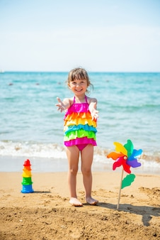 Glimlachend positief meisje van 3 jaar oud in een veelkleurig zwempak en een regenboog in de hand op het zandstrand aan zee
