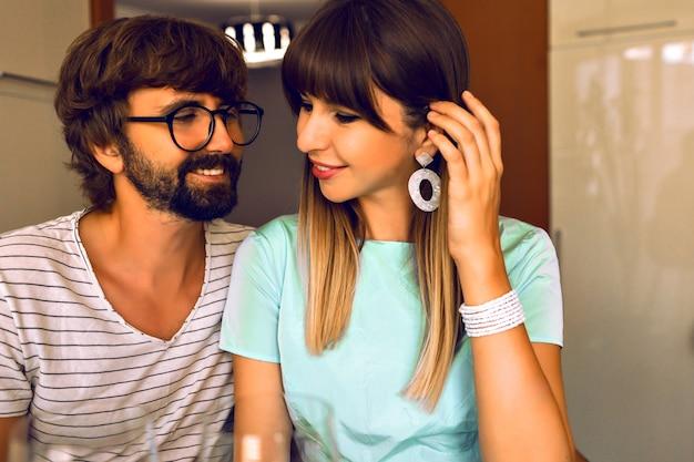 Glimlachend positief verliefde paar, knappe baard man en zijn elegante vrouw genieten van hun romantische avond, elegante kleding, warme kleuren, modern interieur.