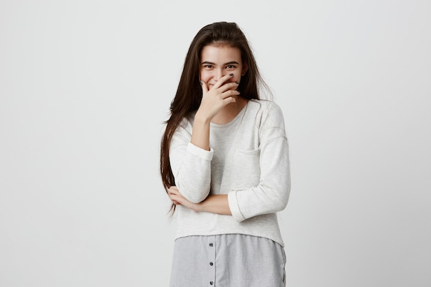 Glimlachend positief wijfje met donker lang haar, die sweater dragen, die tegen grijze muur stellen. gelukkig donkerbruin vrouwen verbergend gezicht achter hand, die positieve emoties tonen na het ontvangen van aangenaam compliment