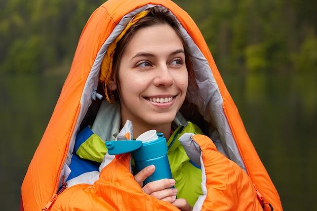 Glimlachend positieve jonge vrouwelijke reiziger verpakt in slaapzak, verwarmt met warme drank tijdens koude herfstdag