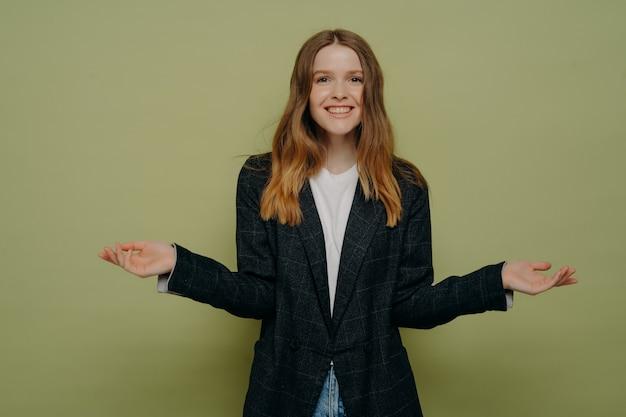 Glimlachend positieve vrouw schouderophalend met gespreide handen en kijkend naar camera met positieve gezichtsuitdrukking, weet niet wat te kiezen terwijl poseren tegen groene studio achtergrond