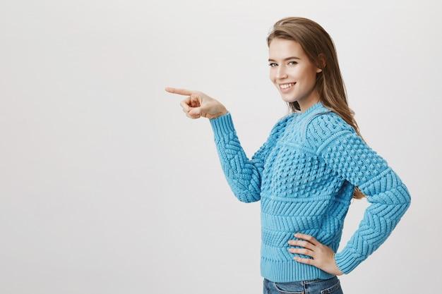 Glimlachend prachtig vrouw permanent profiel, draai naar camera en wijzende vinger naar links