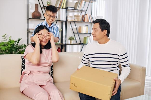 Glimlachend preteen jongen die ogen van moeder behandelt wanneer zijn vader verjaardagsgeschenk geeft