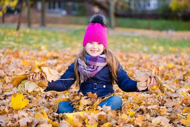 Glimlachend preteen kind spelen in herfst park