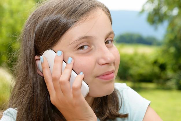 Glimlachend pretienermeisje die smartphone uitnodigen, openlucht