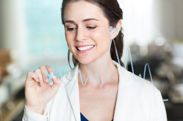 Glimlachend pretty zakenvrouw tekening grafiek op glas