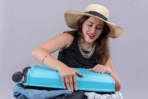 Glimlachend reiziger jong meisje dat zwart onderhemd draagt dat in hoed open koffer op witte achtergrond houdt